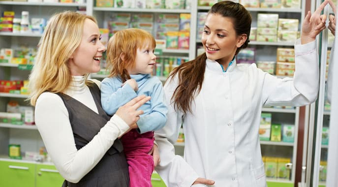 Female Pharmacy Technician demonstrating vitamins to customer in pharmacy drug store