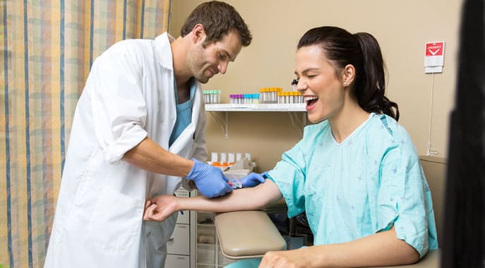 Phlebotomist drawing blood sample in hospital room from young female patient